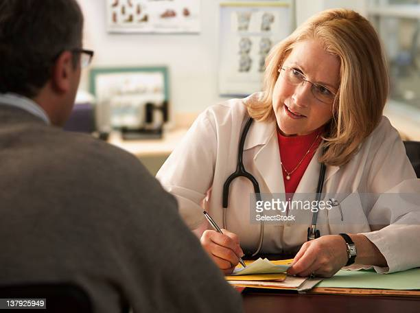 Female Doctor writing notes on male patient