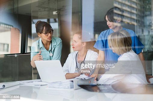Female doctors discussing at laptop desk