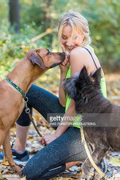 female dog sitter with two dogs in a park