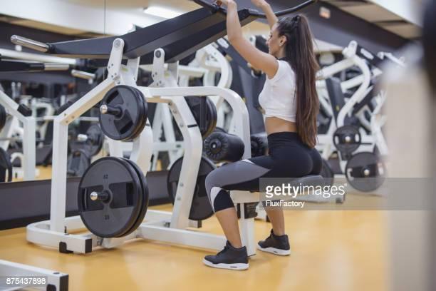 Frauen tun Übungen am Sportgerät im Fitness-Studio