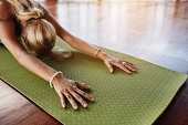 Female doing stretching workout on exercise mat. Woman doing balasana yoga at gym, with focus on hands.