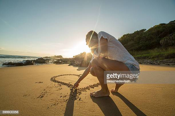 Female drawing heart on sand