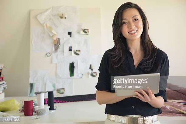 Female dressmaker in studio with digital tablet