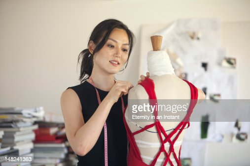 Female dressmaker making alteration in her studio