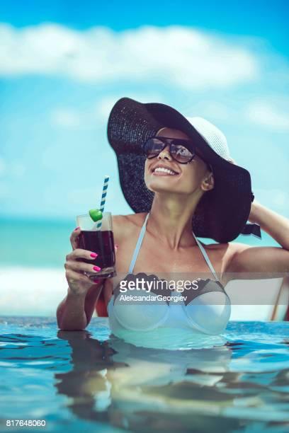 女性のカクテルを飲むとインフィニティ ・ スイミング プールで夕日を楽しむ