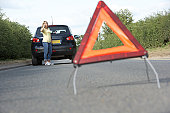 Female Driver Broken Down On Country Road With Hazard Warning Sign In Foreground