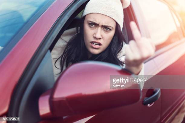 Female driver making obscene gestures while driving on the road