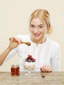 female drizzling honey over healthy breakfast