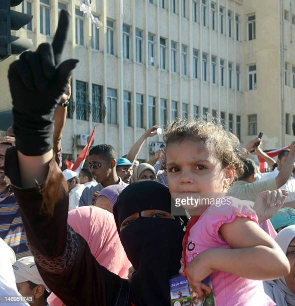 A female Egyptian supporter of Egypt's Muslim Brotherhood candidate Mohamed Morsi holds her daughter as she celebrate in the northern coastal city of...