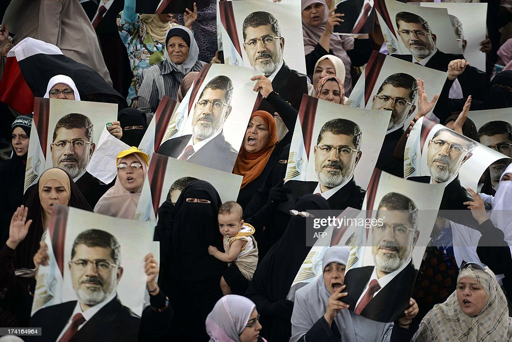Female Egyptian supporters of the Muslim Brotherhood hold up portraits of Egypt's ousted president Mohamed Morsi during a rally in Cairo on July 21, 2013. Supporters of Morsi, who has been held in custody since his ouster on July 3, view the army's decision to overthrow the man they voted into power last year as an affront to democracy.