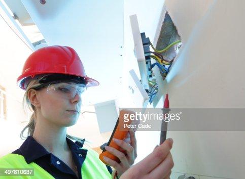 Female electrician checking plug sockets