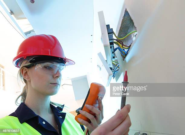 Female electrician checking plug sockets