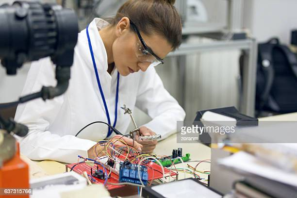 Female electrician working on circuit board at desk
