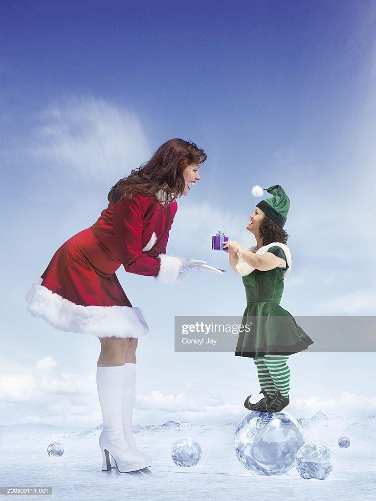Female elf standing on crystal handing present to mother christmas : Bildbanksbilder