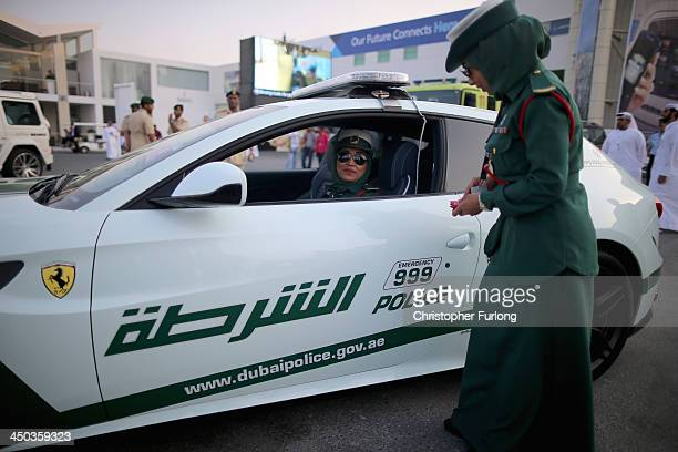 Female Emerati police officers chat as they stand next to their Ferrari supercar during the Dubai Airshow on November 18 2013 in Dubai United Arab...