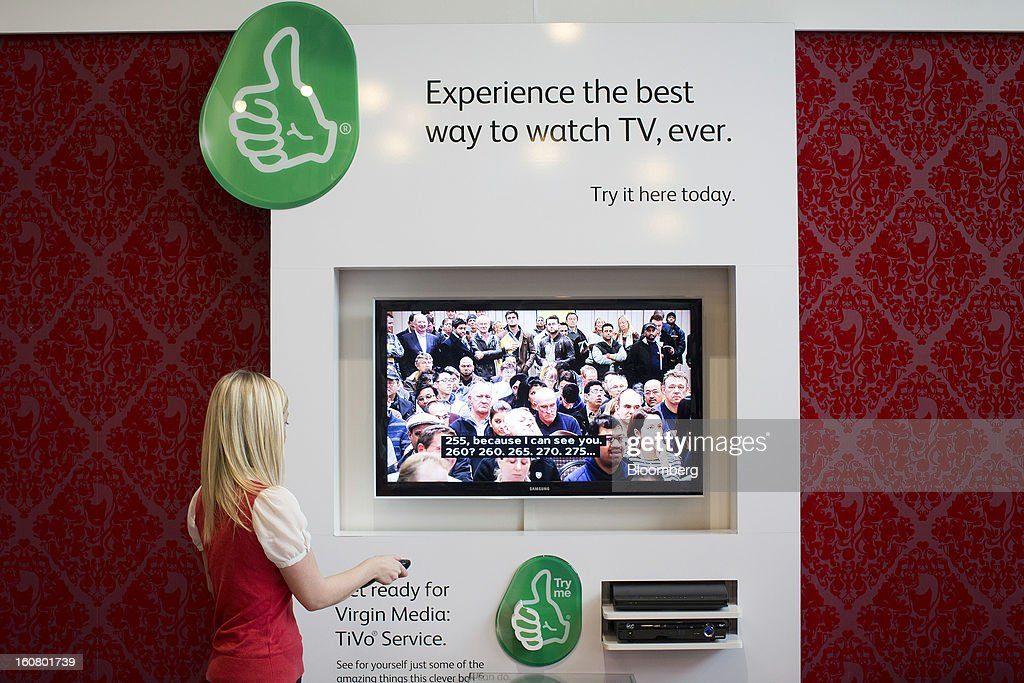 A female employee adjusts a television using the Virgin Media Tivo set-top box inside Virgin Media's reception area at the company's headquarters on the Bartley Wood Business Park in Hook, U.K., on Wednesday, Feb. 6, 2013. Billionaire John Malone's Liberty Global Inc. agreed to acquire Virgin Media, Britain's second-largest pay-TV provider, in a $16 billion cash-and-stock transaction announced in the U.S. yesterday. Photographer: Simon Dawson/Bloomberg via Getty Images
