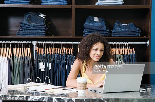 Female employee behind counter in clothing boutique, working on laptop
