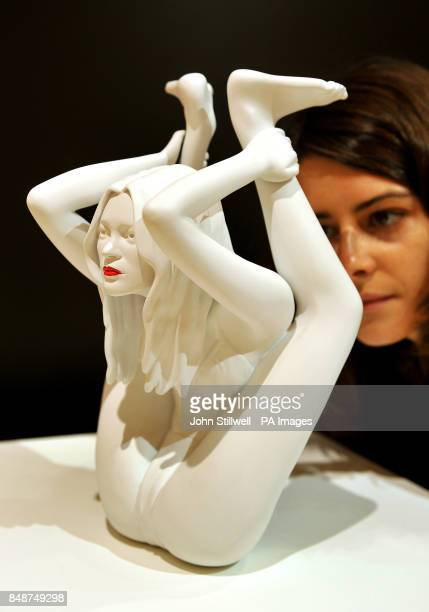 A female employee of Bonham's auctioneers in central London studies a sculpture of supermodel Kate Moss performing Yoga produced by Marc Quinn called...