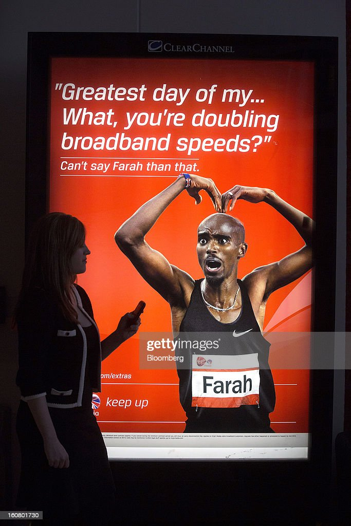 A female employee poses for a photograph with her mobile phone in front of an advert for Virgin Media, starring Olympic athlete Mo Farah, at the company's headquarters on the Bartley Wood Business Park in Hook, U.K., on Wednesday, Feb. 6, 2013. Billionaire John Malone's Liberty Global Inc. agreed to acquire Virgin Media, Britain's second-largest pay-TV provider, in a $16 billion cash-and-stock transaction announced in the U.S. yesterday. Photographer: Simon Dawson/Bloomberg via Getty Images