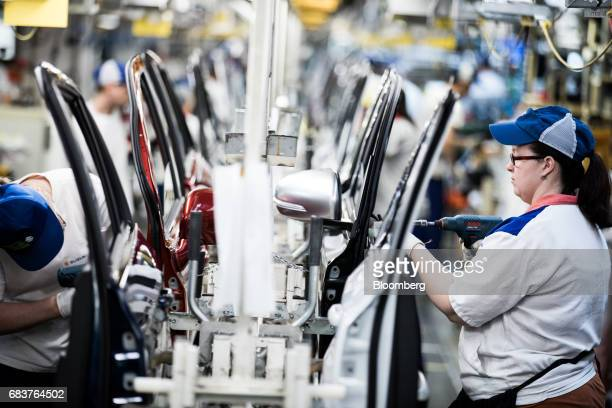 A female employee right works on an automobile door panel on the production line inside the Suzuki Motor Corp plant in Esztergom Hungary on Monday...