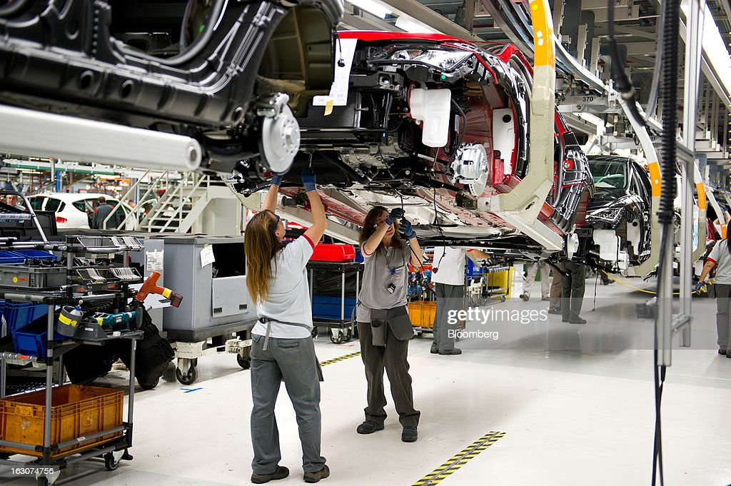 Female employees work on the underside of a Seat Altea XL automobile during assembly on the production line at the headquarters of Seat SA in Martorell, Spain, on Thursday Feb. 28, 2013. Seat will invest 300 million euros a year in the next five years and renew its range of models, Efe said, citing an interview with James Muir, head of the Spanish unit of Volkswagen AG. Photographer: David Ramos/Bloomberg via Getty Images