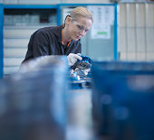 Female engineer assembling small parts of industrial gearbox in engineering factory