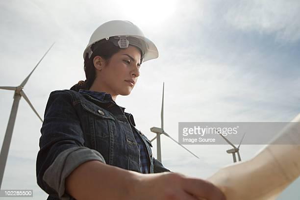 Mujer Ingeniero en wind farm con los planes