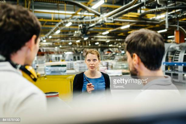 Female Engineer Briefing Manual Worker in Production Line