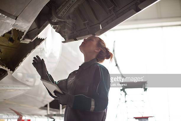 Female engineer inspecting airplane in hangar