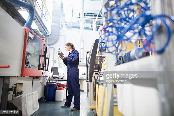 Female engineer monitoring automated machinery using digital tablet
