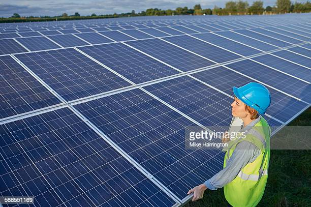Female engineer on solar farm inspecting panel