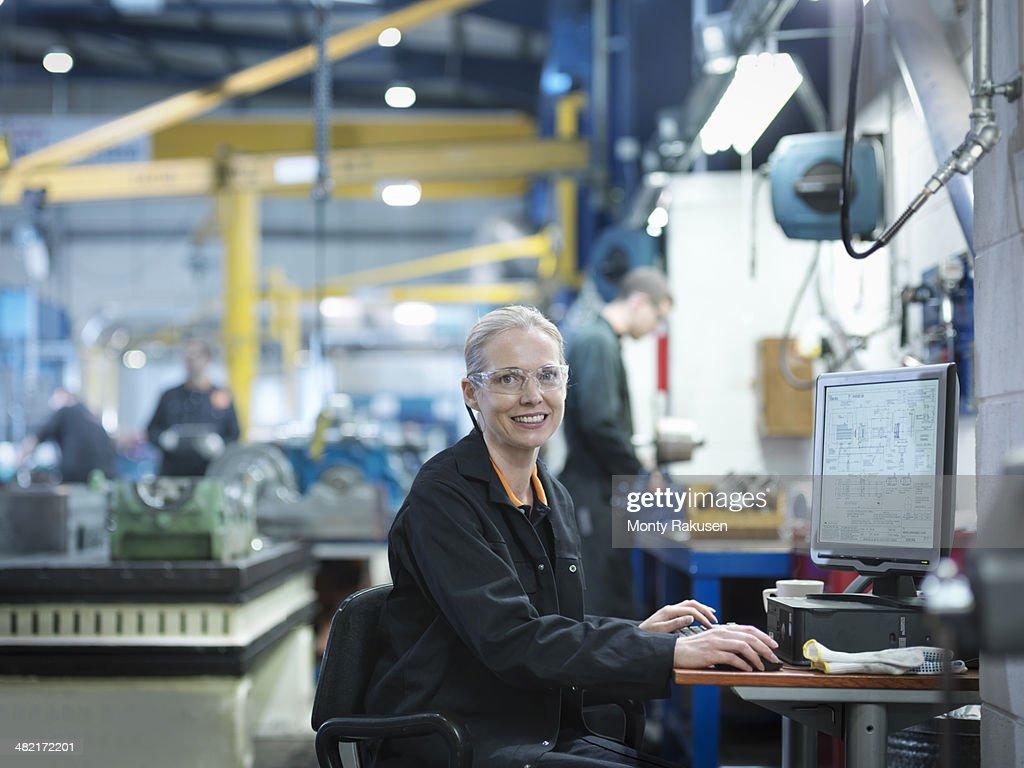 Female engineer using computer in engineering factory, portrait