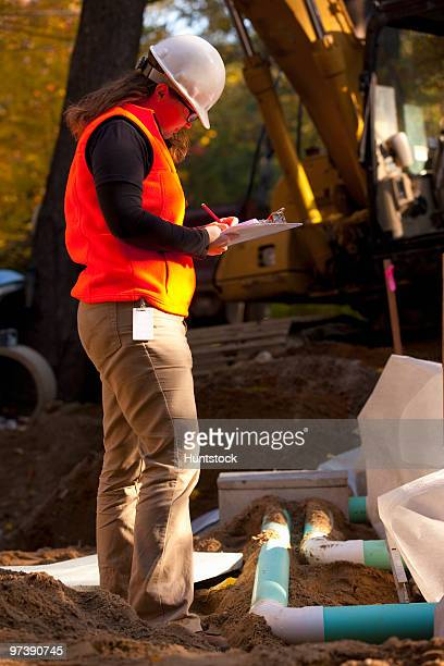 Female engineer writing on a clipboard at a construction site