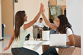 Female engineering students giving high five in the college academic center
