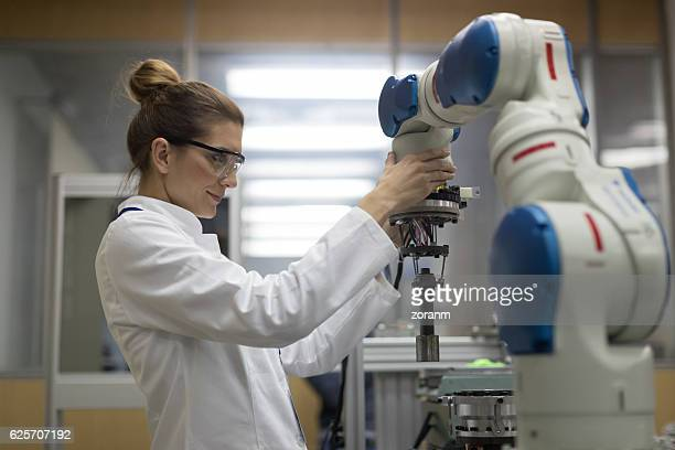 Female engineers working with robotic arm
