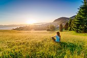 Female enjoying life at sunny morning. Happy young woman at mountains. Relaxation concept