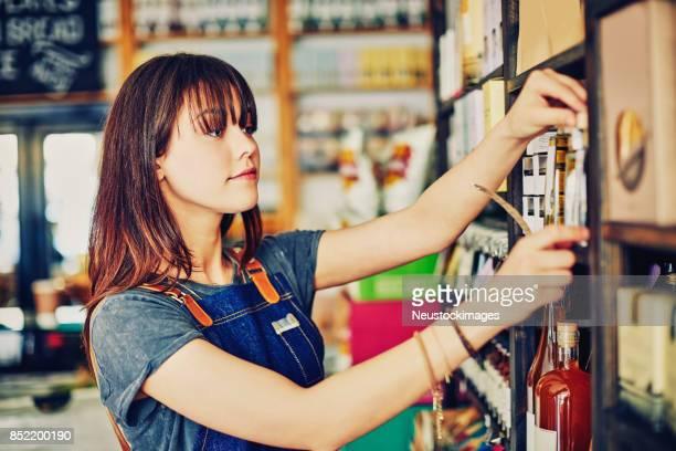 Female entrepreneur arranging infused oil bottles on shelf in deli