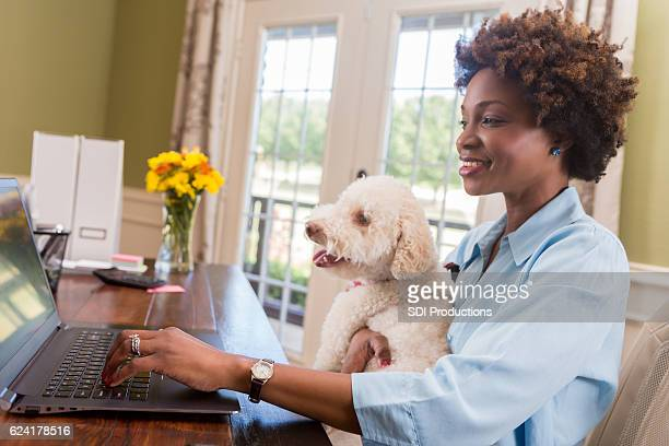 Female entrepreneur holds her dog while working in home office