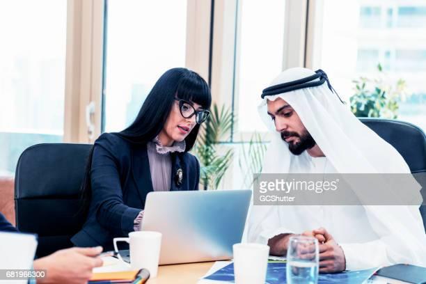 Female entrepreneur presenting business proposal to an emrati arab businessman