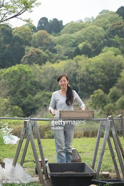 Weibliche Unternehmer Durchsieben Boden für die Verwendung auf einem Bio-Bauernhof