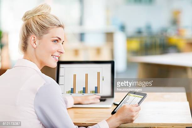 Jeune femme à l'aide d'ordinateur portable et de la tablette numérique dans bureau