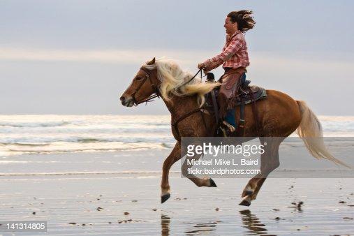 Female equestrian equestrienn brown horse on beach