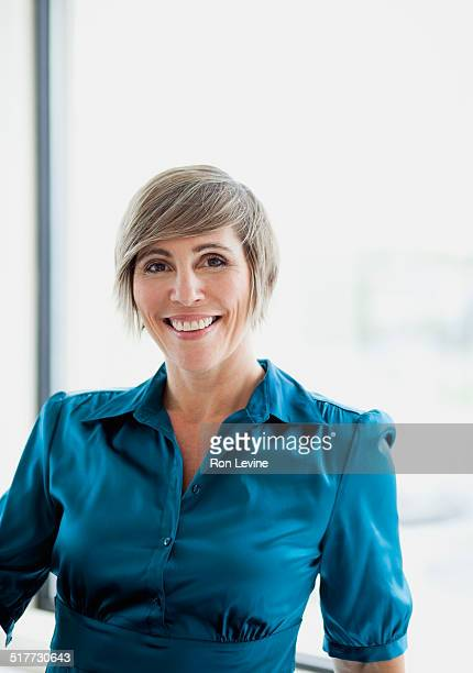 Female executive in office, portrait smiling