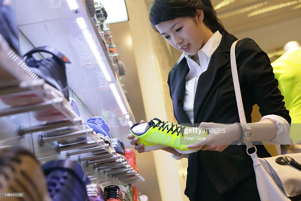 female executive looking at running shoe : Stock Photo