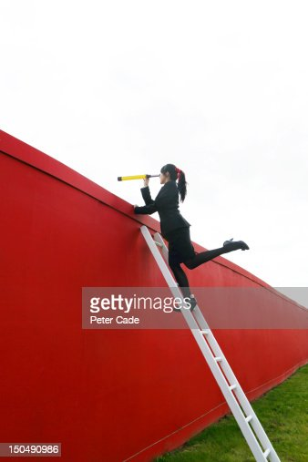 Female executive looking over wall with telescope : Stock Photo