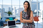 Female executive sitting with arms crossed on desk in the office