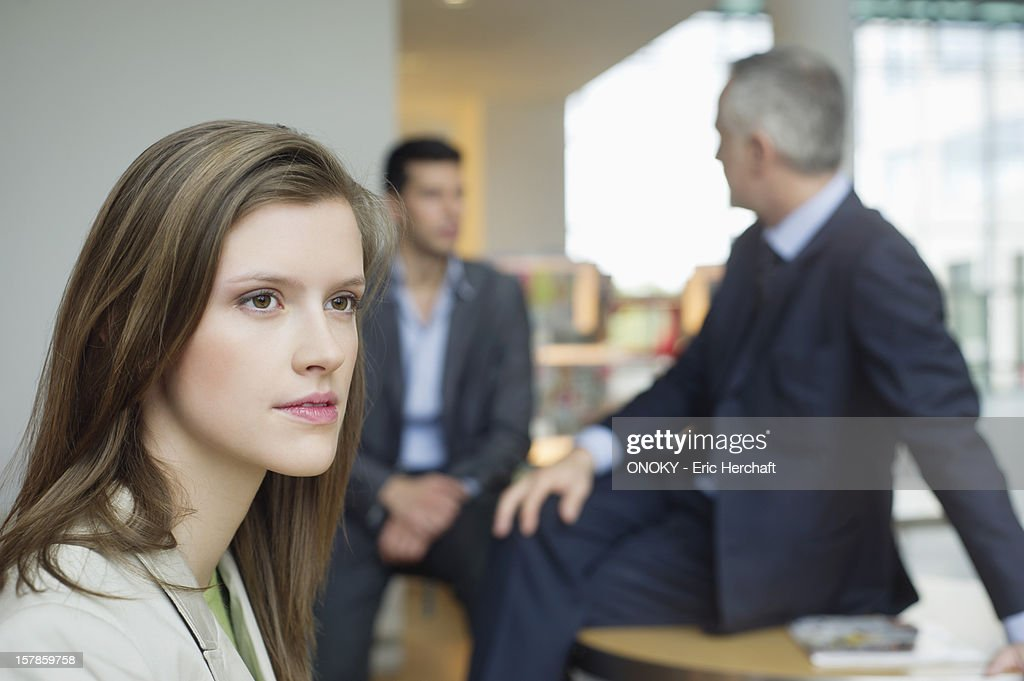 Female executive thinking in an office with her colleagues discussing in the background : Stock Photo