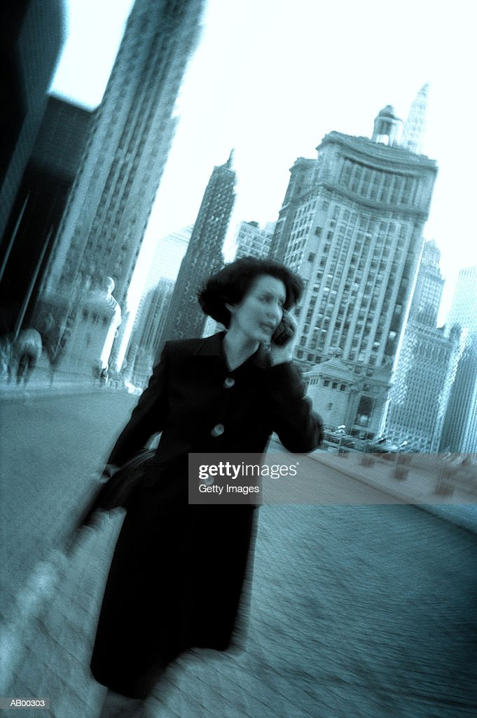 Female executive using mobile phone on street : Stock Photo
