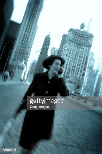 Female executive using mobile phone on street : Stock Photo