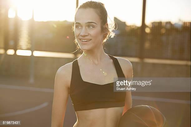 Female exercising in city park, basketball court
